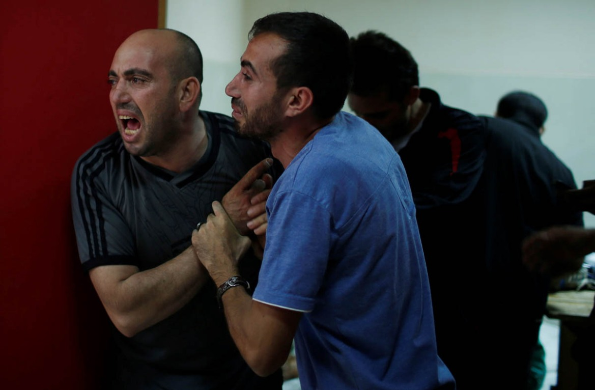 Relatives of a Palestinian killed during a protest at the Israel-Gaza border gather at a hospital in the northern Gaza Strip. [Mohammed Salem/Reuters]