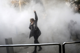 A university student attends a protest inside Tehran University while a smoke grenade is thrown by anti-riot Iranian police, in Tehran, Iran, on December 30, 2017 [AP]