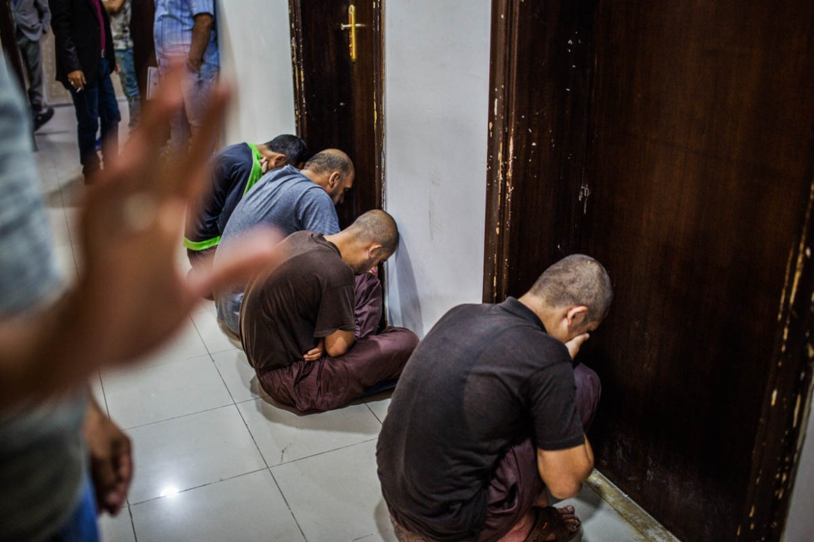 Before entering the courtroom at the Central Criminal Court of Baghdad, prisoners wait in a corridor. [Alessio Mamo/Al Jazeera]