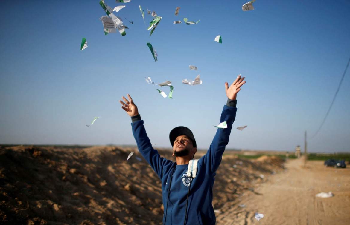 A Palestinian man throws leaflets dropped by the Israeli military during a protest against the US embassy move to Jerusalem. [Mohammed Salem/Reuters]