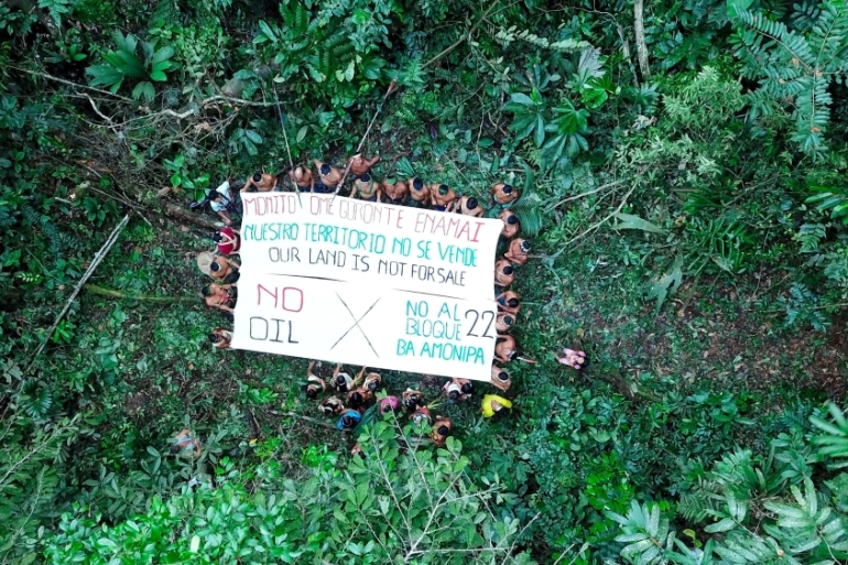 An aerial shot of the Waorani community of Nemonpare holding a banner protesting the sale of land in block 22, which overlaps Waorani territory [Courtesy of Amazon Frontlines]