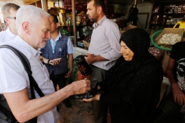 A Syrian refugee offers sweets to Jeremy Corbyn during his visit to Al Zaatari refugee camp, in the Jordanian city of Mafraq, near the border with Syria, June 22, 2018 [Muhammad Hamed/Reuters]