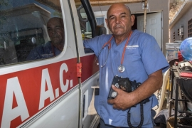 Panchito takes out the radio he had left in the ambulance; it doesn't work anymore either and needs to be repaired [Eline van Nes/Al Jazeera]