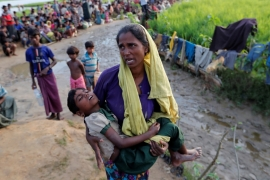 A Rohingya refugee woman who crossed the border from Myanmar a day before, carries her daughter and searches for help, in Palang Khali, Bangladesh October 17, 2017 [Reuters]