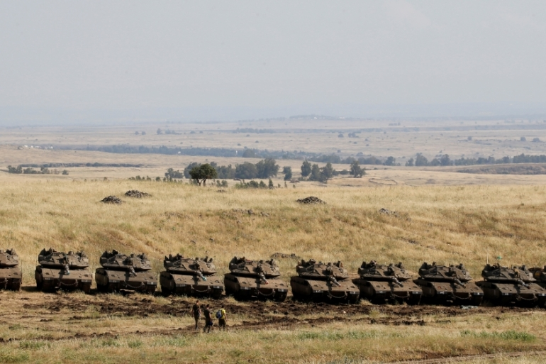 Israeli soldiers walk past tanks near the border with Syria in the Israeli-occupied Golan Heights [File: Reuters]