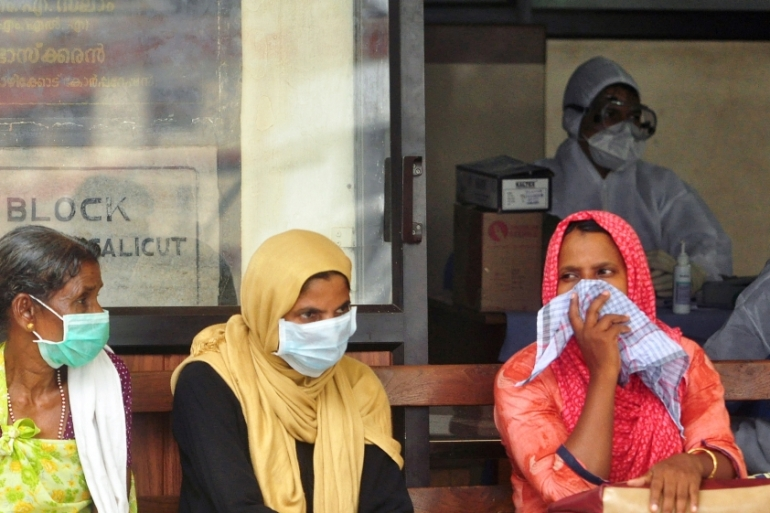 People wear masks as they wait outside a casualty ward at a hospital in Kozhikode in the southern state of Kerala [REUTERS/Stringer]
