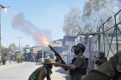 An Indian policeman fires a tear gas shell towards protesters in Kashmir's Pulwama district on April 7, 2018 [Danish Ismail/Reuters]