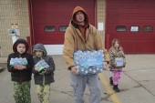 A local family carry bottled water they picked up from a fire station in Flint, Michigan February 7, 2016 [Rebecca Cook/Reuters]