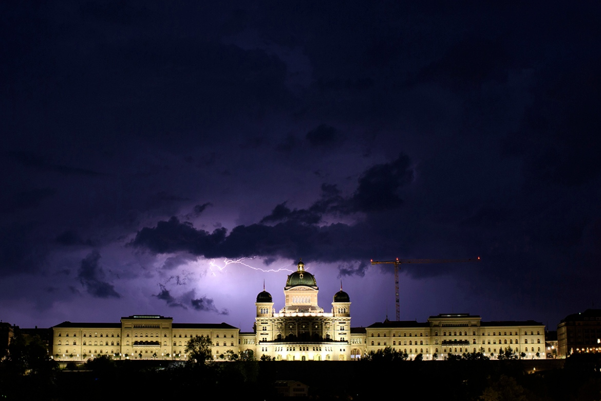 Federal Palace in Bern illuminated by a dramatic thunderstorm. [Anthony Anex/EPA]