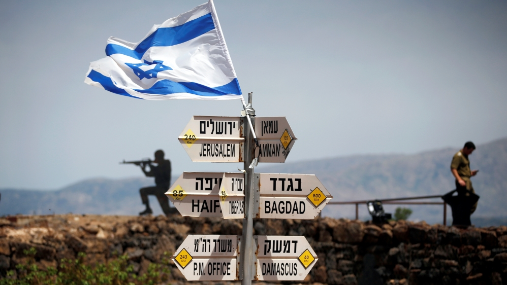 An Israeli soldier stands next to signs showing distances to different cities, on Mount Bental, an observation post in the Israeli-occupied Golan Heights overlooking the Syrian side of the Quneitra crossing [File: Reuters]