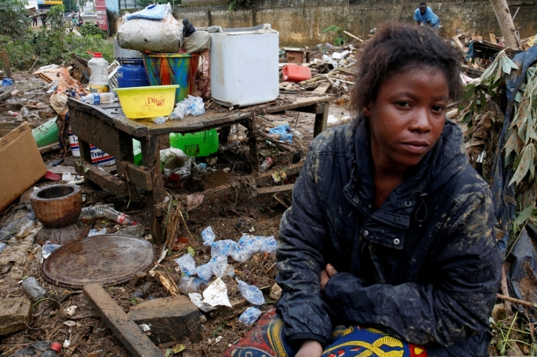A woman sits between her belongings and the debris after flood in Abidjan, Ivory Coast, June 19, 2018 [Luc Gnago/Reuters]