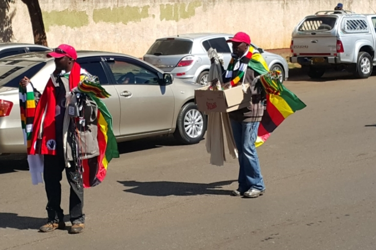 Street sellers benefit from the high demand for flags and party scarfs before the vote [Hamza Mohammed/Al Jazeera]