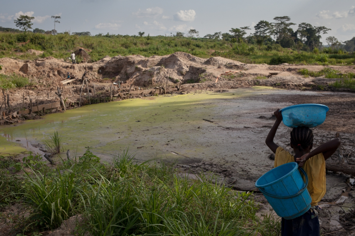 A girl walks in Gerwane's gold mine, near the Kambele 2 village, Cameroon. The whole Kadey prefecture, known for its gold and wood resources, is home to refugees from the CAR. [Adrienne Surprenant/Al Jazeera]