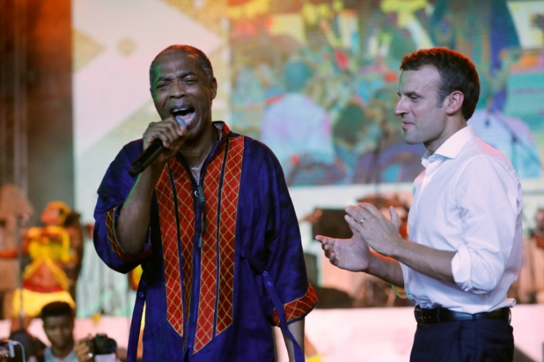 French President Emmanuel Macron stands on stage as Fela Kuti's son, Femi Kuti, performs at the New Afrika Shrine in Lagos, Nigeria on July 3, 2018 [Akintunde Akinleye/Reuters]