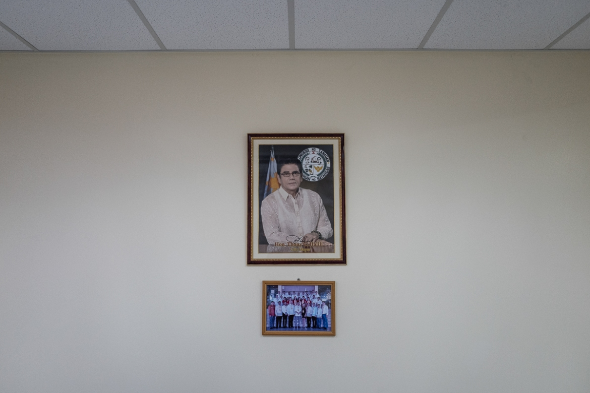 A picture of Tanauan Mayor Antonio Halili hangs on a wall inside his office in Batangas province, just outside Manila. [Ezra Acayan/Al Jazeera]