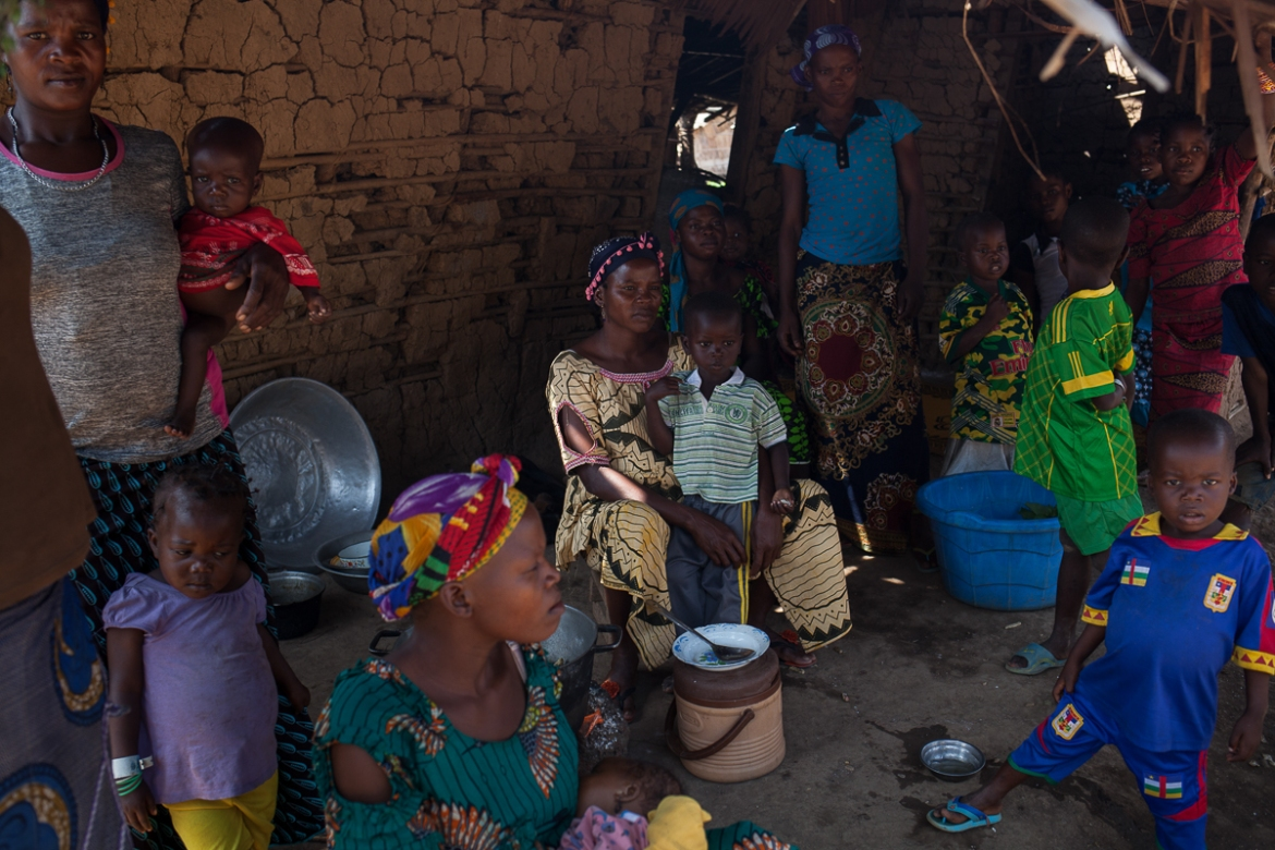 A family sits and eat in the shadow of Emmanuel Bale Nguia's house, in Bombe Chateau. Bale Nguia fled his village the CAR in 2013. The rest of his family of 40 joined him in Cameroon on May 17, running away as they heard approaching gunshots. One of his brothers-in-law died as he stayed behind to try and pack a few belongings. Emmanuel offered them a house to stay in and helps the widow with a bit of food, but his meagre salary is insufficient to feed the whole group of recently arrived refugees. [Adrienne Surprenant/Al Jazeera]