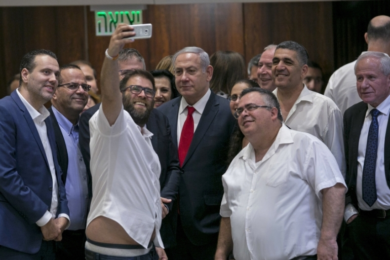 Knesset member Oren Hazan takes a selfie with Israel's Prime Minister Benjamin Netanyahu after a Knesset session that passed the 'nation-state' bill in Jerusalem on July 19 [AP Photo/Olivier Fitoussi]