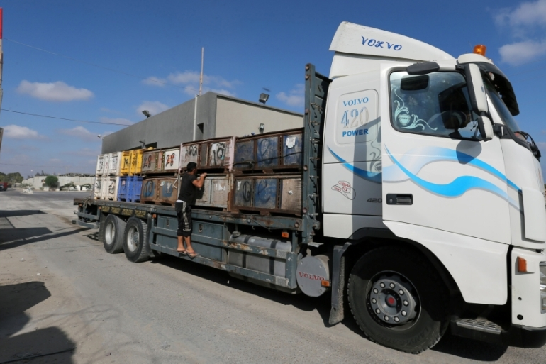 A truck carrying fruits arrives at Kerem Shalom crossing in the southern Gaza Strip [Ibraheem Abu Mustafa/Reuters]