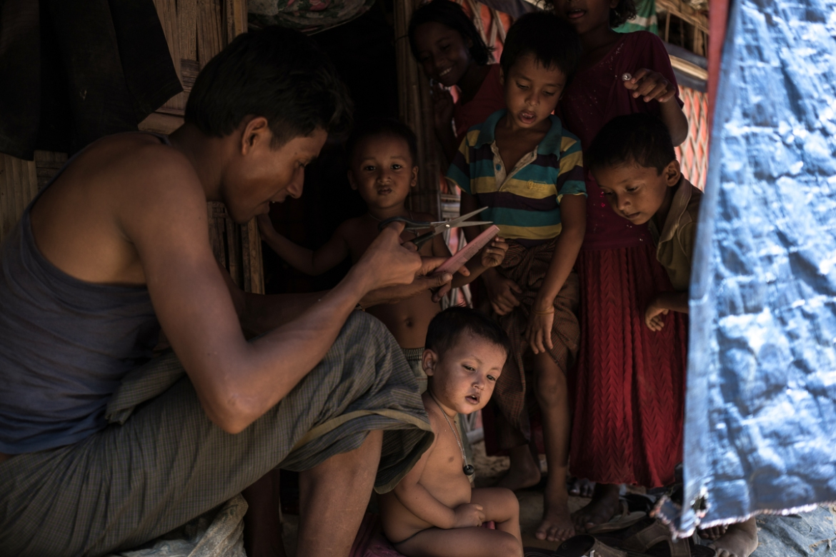 A Rohingya refugee cuts his young son's hair in front of their shelter, deep in the Balukhali camp. The UN's refugee agency estimates that children make up 55 percent of the total refugee population. [Sorin Furcoi/Al Jazeera]
