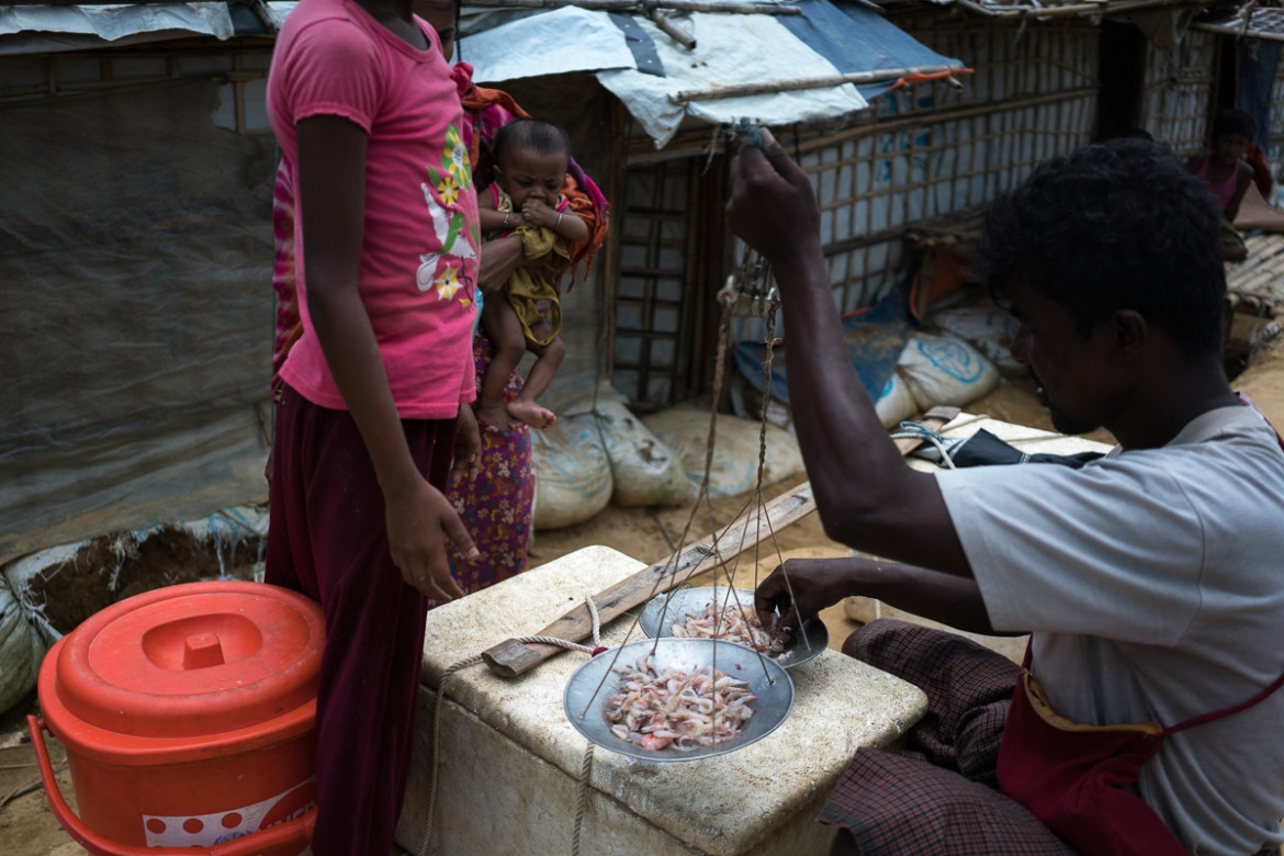 A Rohingya refugee sells freshwater prawns caught in the small streams around the refugee camps. [Sorin Furcoi/Al Jazeera]