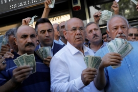 Businessmen line up in front of a currency exchange office in Ankara in response to the call of Turkish President Erdogan on Turks to sell foreign currency to support the lira [Reuters/Umit Bektas]