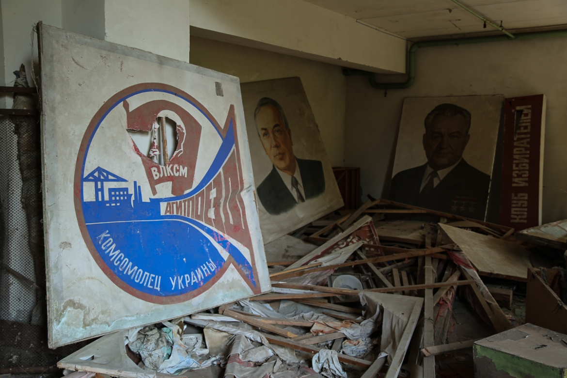 Soviet-era posters and signs in Pripyat's ruined community theatre. [Blake Sifton/Al Jazeera]