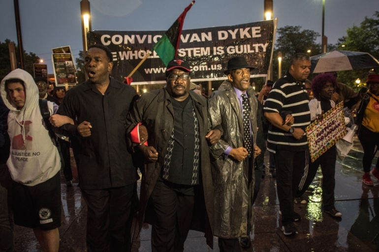 Protesters, including Pastor Ira Acree, second from left, Rev Marshall Hatch, centre, and Eric Russell of Tree of Life Justice League, march towards the Cook County Courthouse in Chicago, Illinois at a vigil for Laquan McDonald [Jason Patinkin/Al Jazeera]