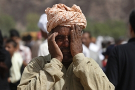 A member of the Ahmadiyya community weeps after burying the dead at a graveyard in Chenab Nagar, northwest of Lahore [File: Reuters]