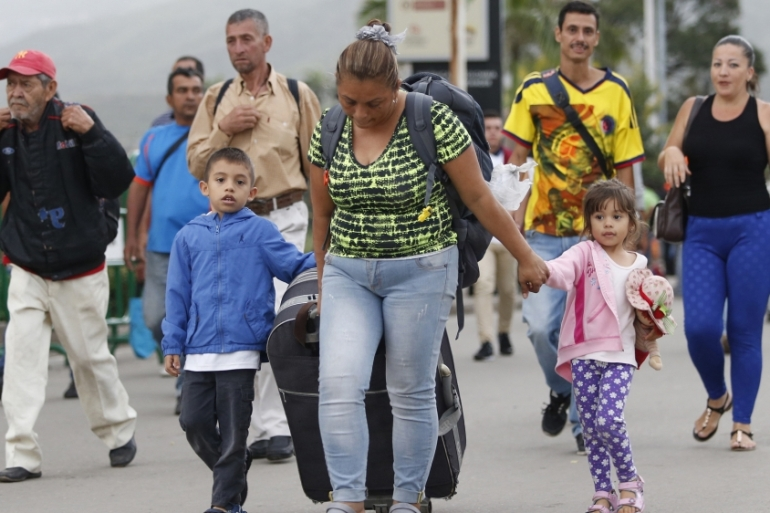 A Venezuelan migrant mother crosses the Simon Bolivar International Bridge into Colombia with her children and luggage, to Cucuta, Colombia, as they leave Venezuela [Fernando Vergara/AP Photo]