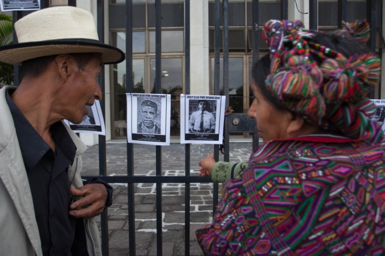 An Ixil Maya woman and man look at photos of missing people from Guatemala's internal armed conflict [Jeff Abbott/Al Jazeera]