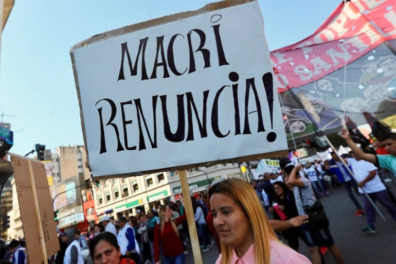 A woman holds up a sign that reads 'Macri, resign!' as she takes part in a demonstration against the government's austerity measures in Buenos Aires, Argentina [Marcos Brindicci/Reuters]