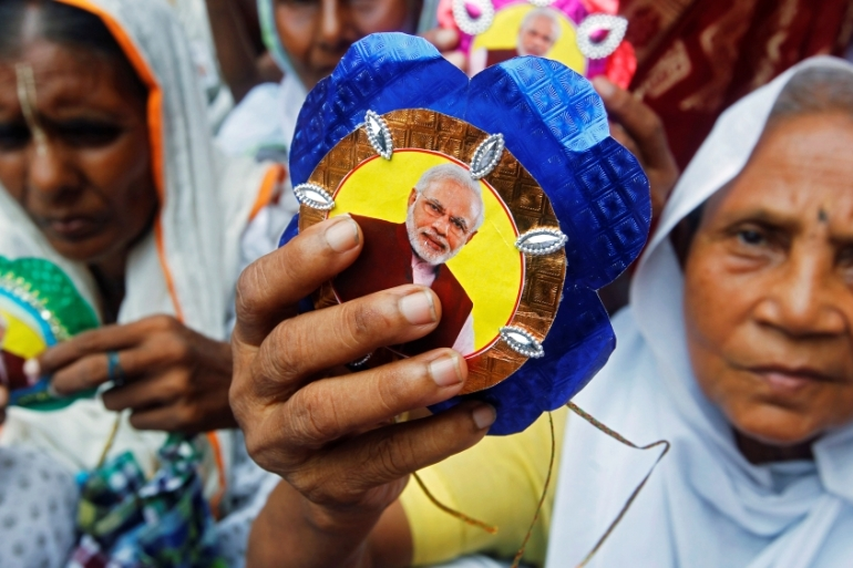 Women show rakhis or sacred threads with a picture of Indian Prime Minister Narendra Modi at a temple in Vrindavan in the Indian state of Uttar Pradesh on August 17, 2016 [Jitendra Prakash/Reuters]