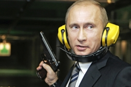 Russian President Vladimir Putin stands with a gun at a shooting gallery of the new GRU military intelligence headquarters building as he visits it in Moscow November 8, 2006. [Reuters]