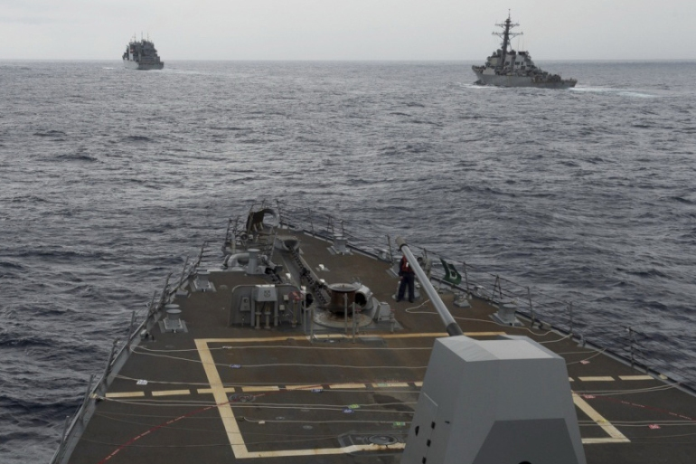 The guided missile destroyer USS Decatur, right, is photographed in 2016 in the South China Sea [Will Gaskill via AP]