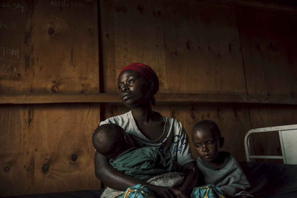 Esther waits with her children outside a Save the Children health clinic in a camp for communities displaced by conflict. [Hugh Kinsella Cunningham/Save the Children]