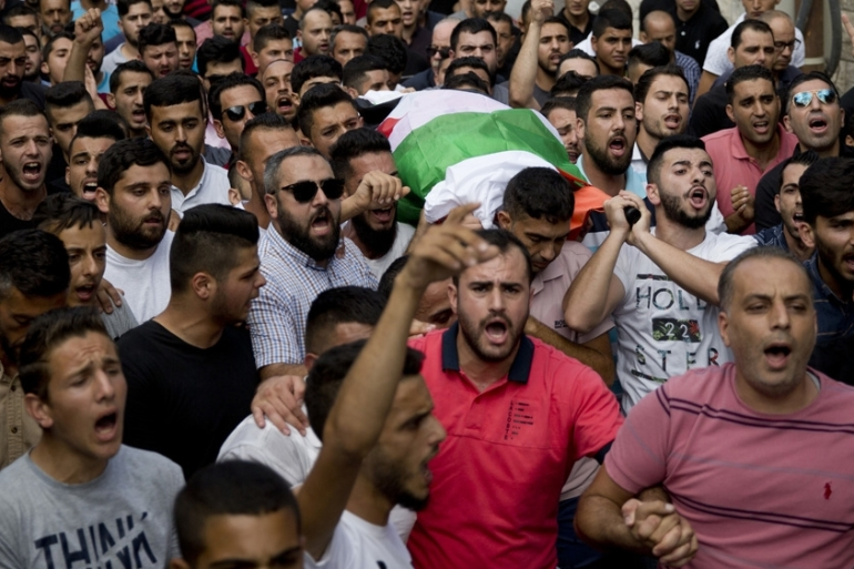 In this file photo from October, Palestinians carry the body of Aisha al-Rawbi, 47, during her funeral in the West Bank village of Biddya [File: Majdi Mohammed/AP Photo]
