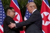 US President Donald Trump shakes hands with North Korean leader Kim Jong Un at the Capella Hotel on Sentosa island in Singapore June 12, 2018 [Jonathan Ernst/Reuters]