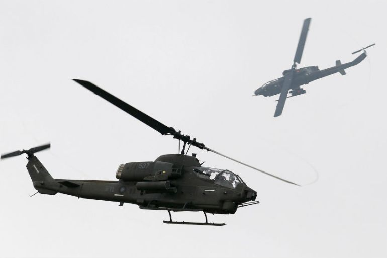 Apache AH-64E attack helicopters fly during a military drill in Taoyuan city, northern Taiwan, on Tuesday [Chiang Ying-ying/AP]