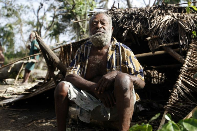 Village chief Philip Kasamu poses on a smashed hut destroyed by Cyclone Pam on the island of Tanna, Vanuatu in 2015 [File: Nick Perry/AP]
