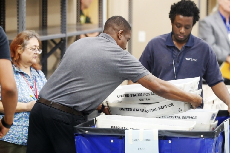 Employees at the Broward County Supervisor of Elections office move bins of sorted ballots [Wilfredo Lee/AP Photo]
