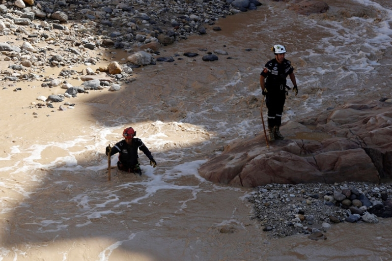 Civil defence members looked for survivors after rain storms unleashed the flash floods [Muhammad Hamed/Reuters]