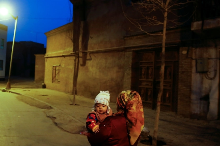 A woman carries a child at night in the old town of Kashgar last year [Thomas Peter/Reuters]