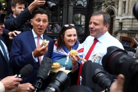 Arron Banks and Andy Wigmore, who ran the Leave.Eu Brexit referendum campaign, eat pork pies as they arrive to give evidence to the Digital Culture Media and Sport Parliamentary Committee [Reuters]