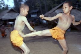 Two novice Buddhist monks practice Muay Thai in northern Thailand [David Longstreath/AP]