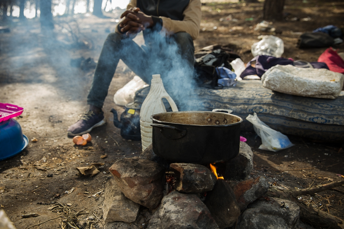 Wood collected from the forest is used for fuel to cook the lunch that is often these migrants' only meal of the day. [Faras Ghani/Al Jazeera]