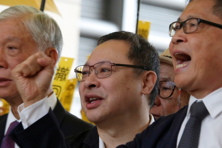 Occupy Central pro-democracy movement founders (left to right) Chu Yiu-ming, Benny Tai and Chan Kin-man chant slogans outside a court in Hong Kong [Bobby Yip/Reuters]