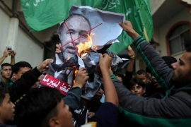 Palestinians burn a poster depicting Israel's Defence Minister Avigdor Lieberman as they celebrate his resignation in Gaza City on November 14, 2018 [Suhaib Salem/Reuters]