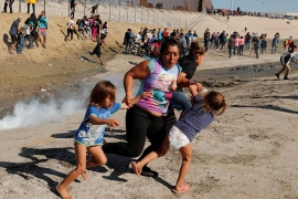 A family run away from tear gas in front of the border wall between the US and Mexico in Tijuana [Kim Kyung-Hoon/Reuters]