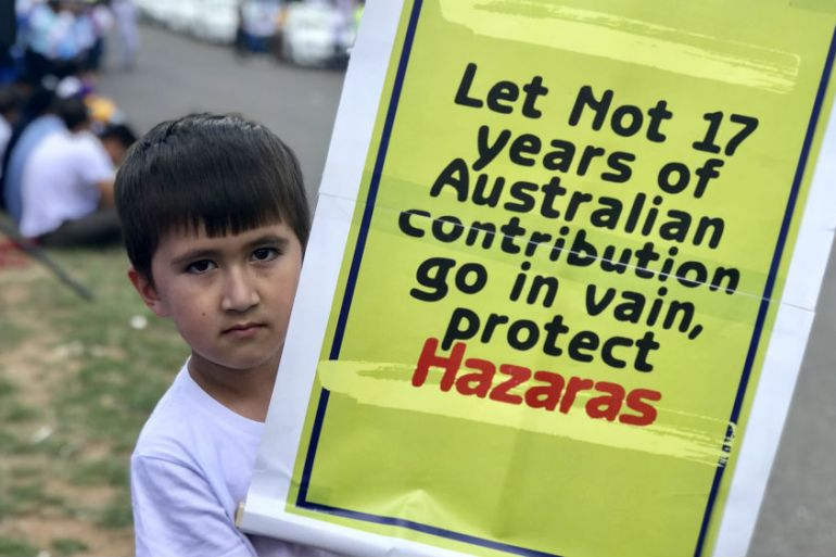 A Hazara boy stands with a placard at a protest in the capital Canberra on Monday [Courtesy: Keyhan Farahmand]