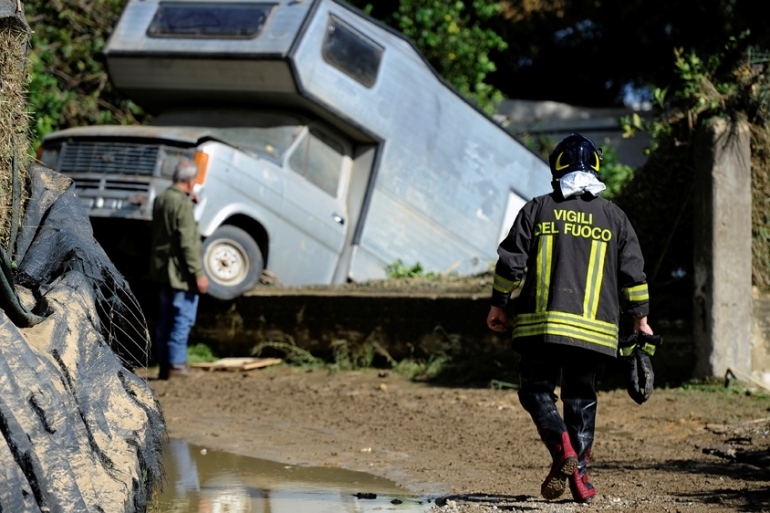A firefighter walks in the mud in the aftermath of a flood in Casteldaccia near Palermo [Guglielmo Mangiapane/Reuters]